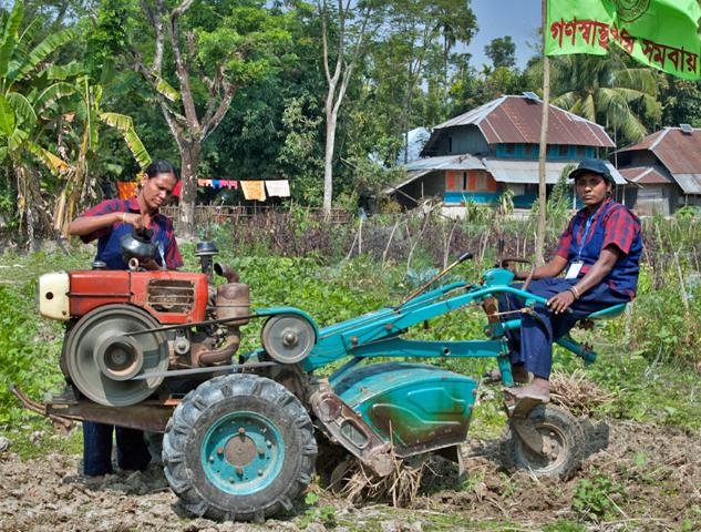 deux femmes Bangladaises s'occupant des champs sur leur tracteur