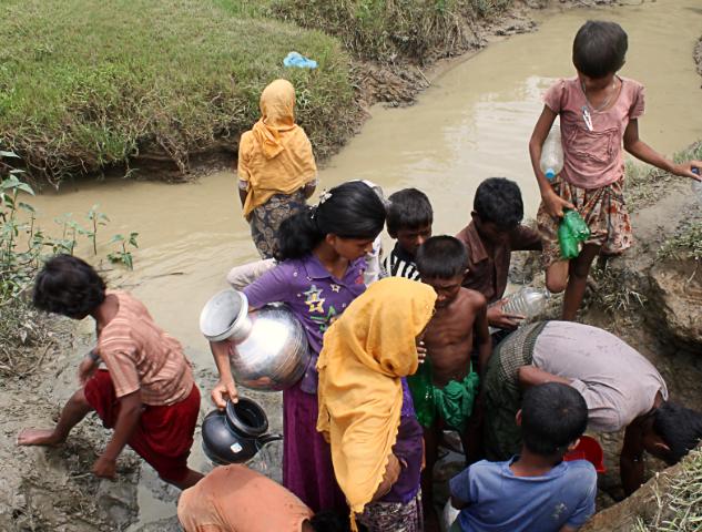 femmes, enfants, hommes Bangladais regroupés autour d'une source d'eau naturelle
