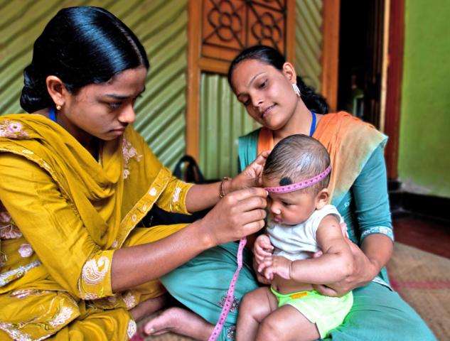 femme Bangladaise paramédic qui osculte un bébé tenu dans les bras de sa maman